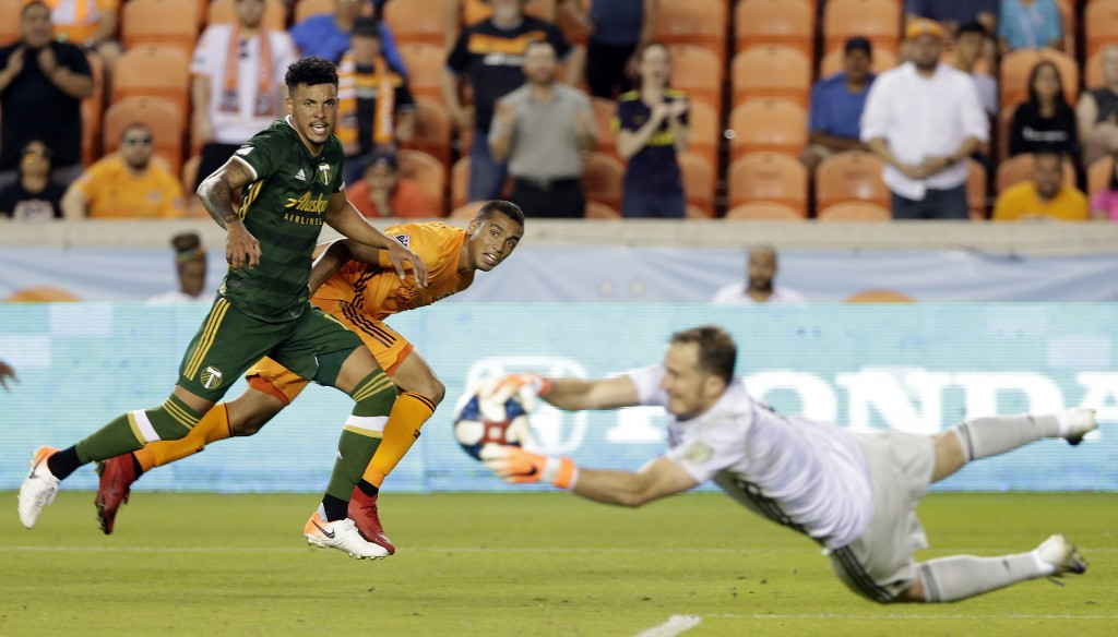 Portland Timbers defender Julio Cascante, left, and Houston Dynamo forward Mauro Manotas, middle, watch as Timbers goalkeeper Jeff Attinella, right, c