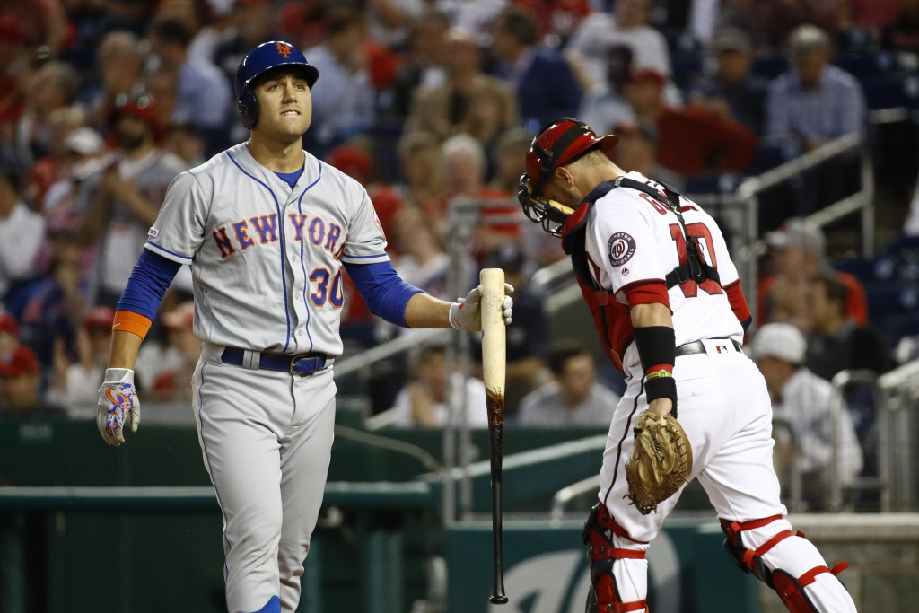 New York Mets' Michael Conforto, left, walks off the field past Washington Nationals catcher Yan Gomes after striking out swinging in the fourth innin...