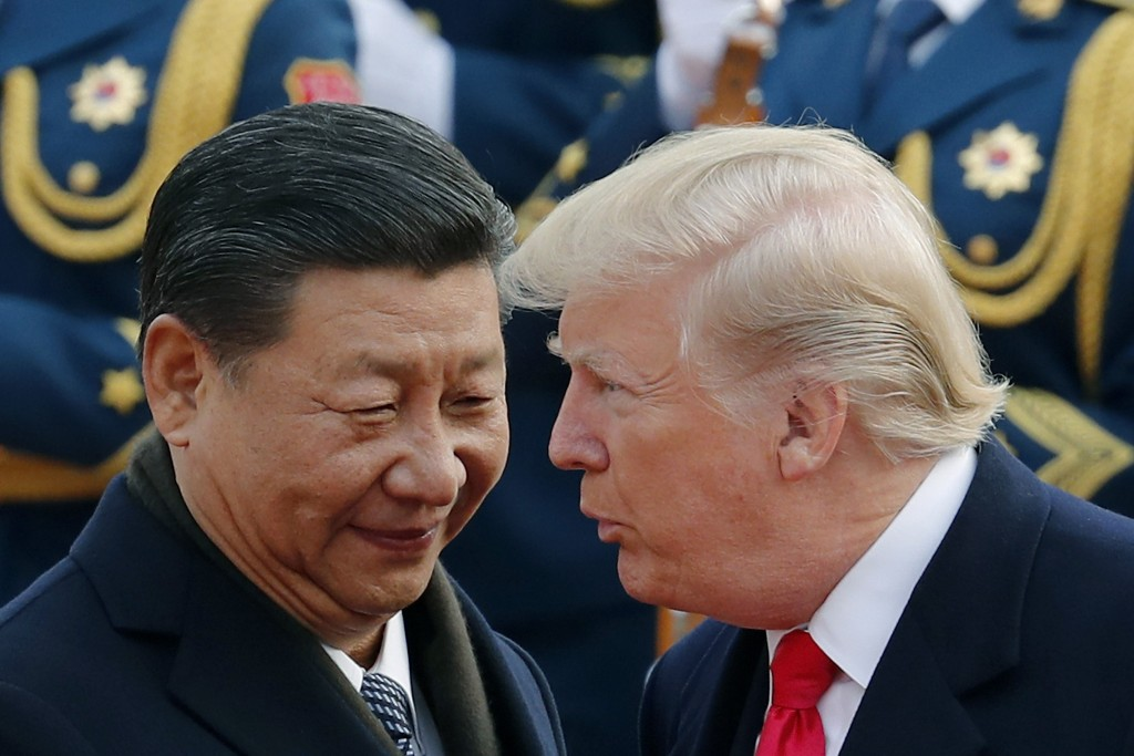 FILE - In this Nov. 9, 2017, file photo, U.S. President Donald Trump, right, chats with Chinese President Xi Jinping during a welcome ceremony at the