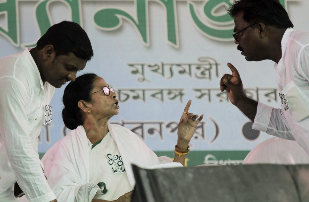 Trinamool Congress leader and Chief Minister of West Bengal state Mamata Banerjee talks to a party member at an election rally at Anchana in Mathurapu