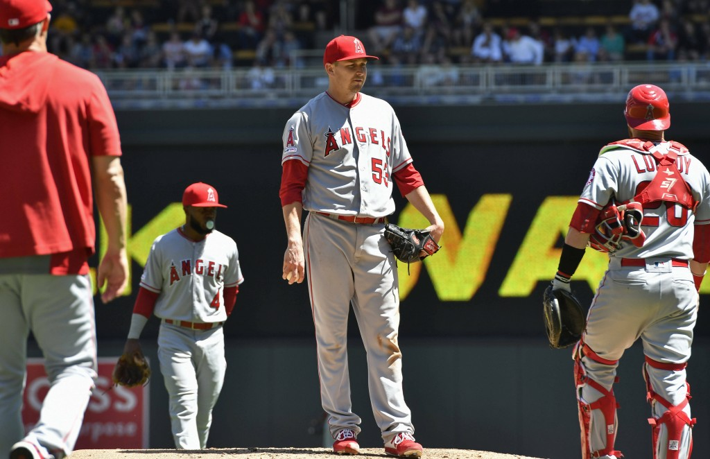 Los Angeles Angels pitcher Trevor Cahill, center, waits to be pulled by manager Brad Ausmus, left, after giving up a walk to Minnesota Twins' C.J. Cro