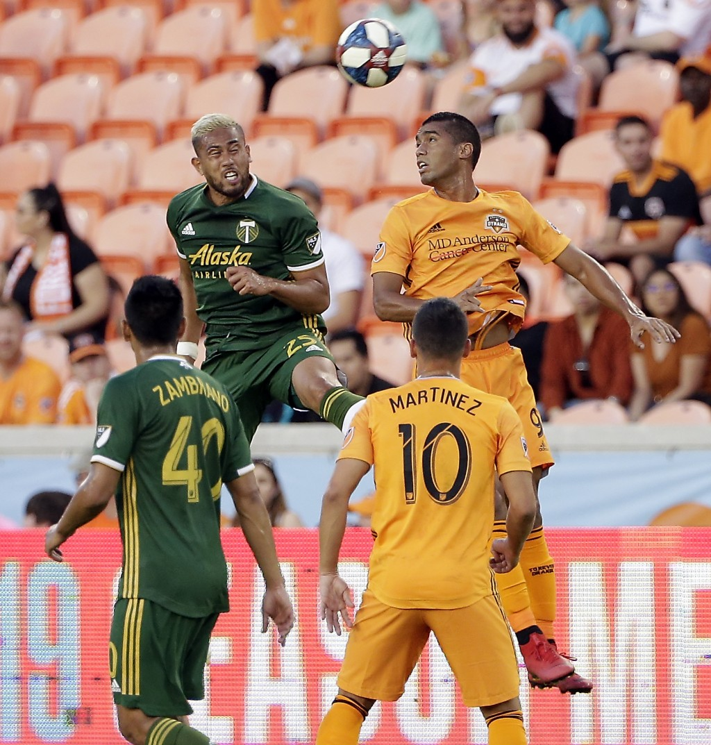Portland Timbers defender Bill Tuiloma (25) and Houston Dynamo forward Mauro Manotas (9) go up for a header in front of Portland midfielder Renzo Zamb