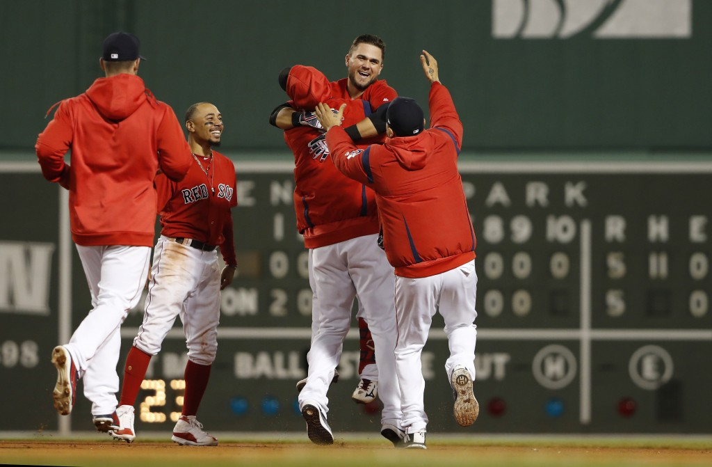 Boston Red Sox's Michael Chavis, second from right, is mobbed by teammates after his game-ending RBI single during the 10th inning of a baseball game