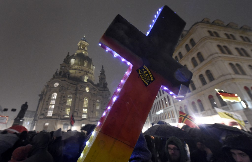 """FILE - In this Monday, Feb. 29, 2016 file photo, an illuminated cross with a sticker reading """"Refugees not welcome"""" is displayed during a demonstratio"""