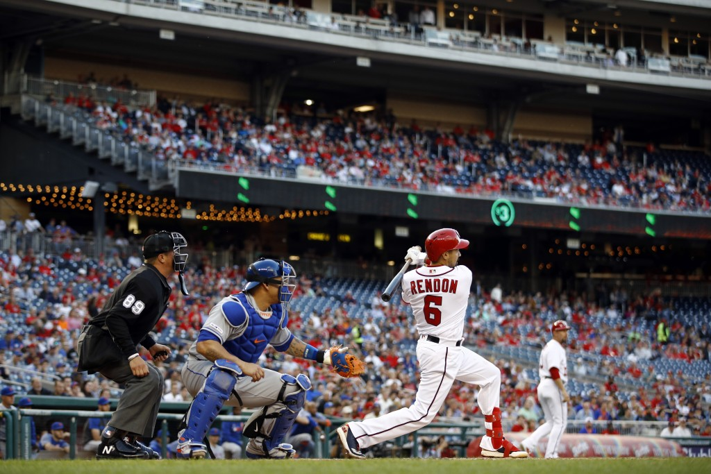 Washington Nationals' Anthony Rendon, right, hits a ground rule double in front of New York Mets catcher Wilson Ramos and home plate umpire Cory Blase...