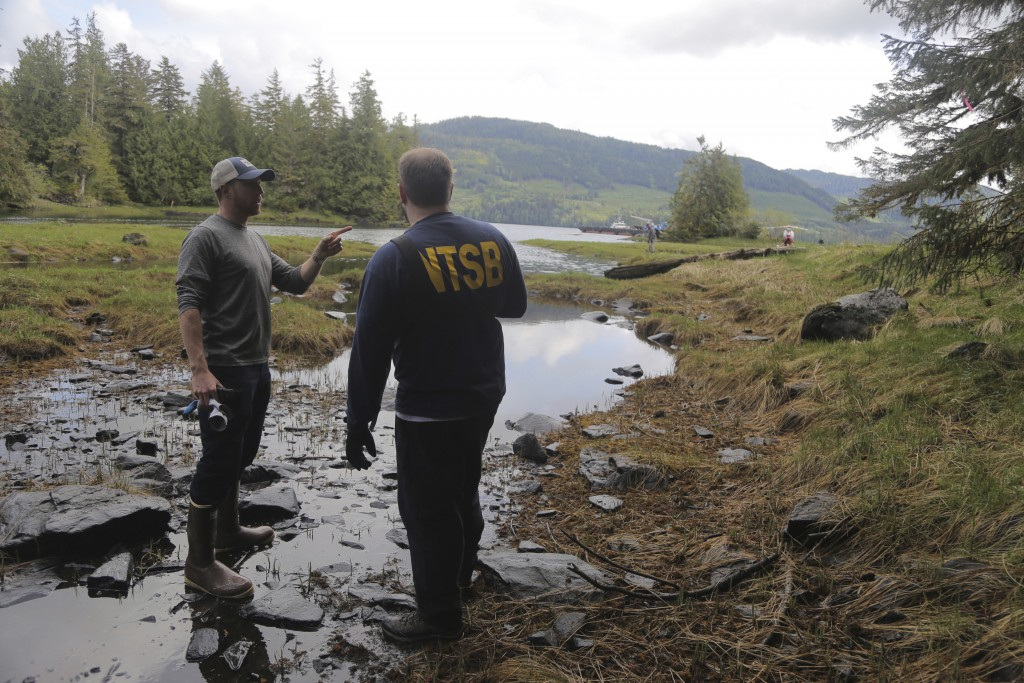 In this photo provided by the National Transportation Safety Board, NTSB investigators Josh Lindberg, left, and Eric Swenson discuss, Wednesday, May 1...