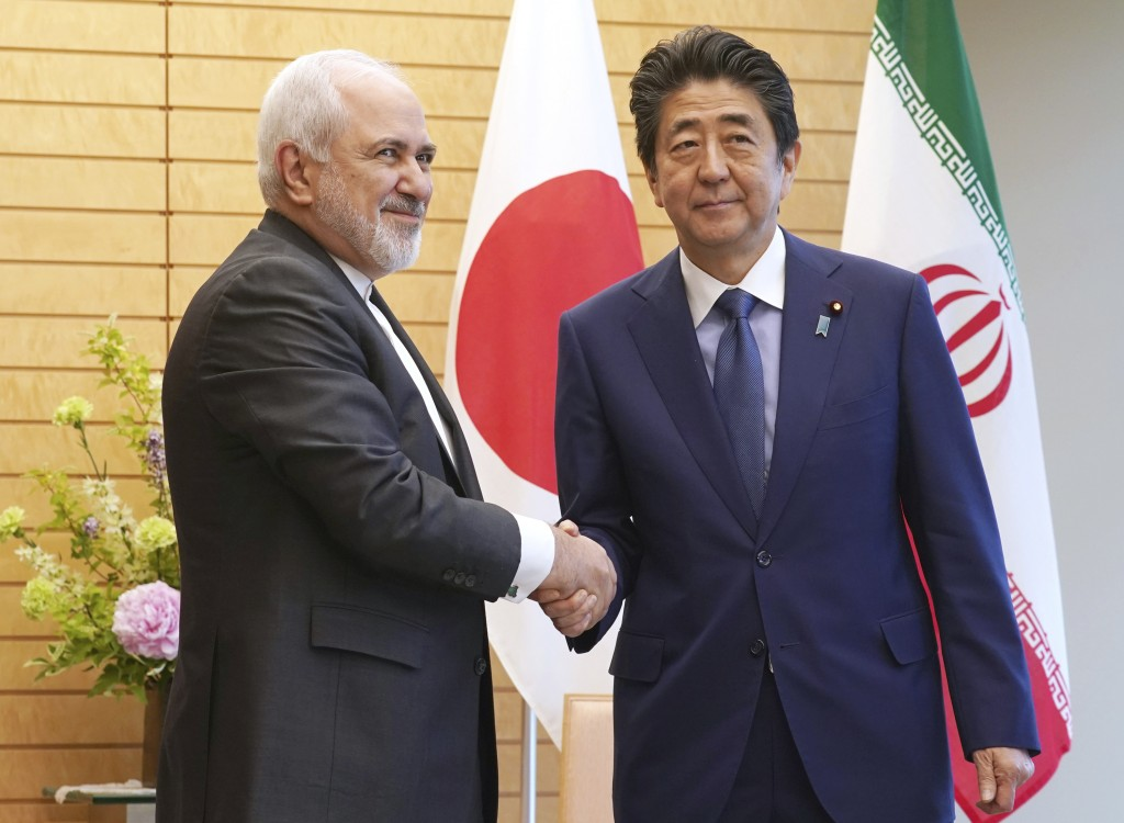 Iranian Foreign Minister Mohammad Javad Zarif, left, and Japanese Prime Minister Shinzo Abe, right, shake hands at Abe's official residence in Tokyo T