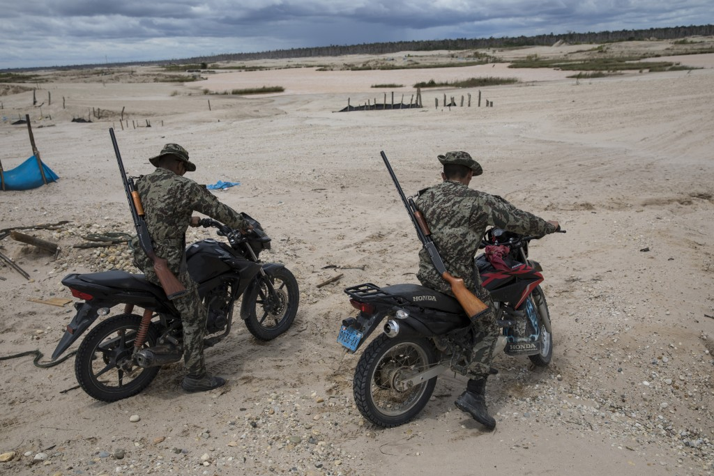 "In this March 27, 2019 photo, ""Operation Mercury"" soldiers patrol on motorbikes an area once used by illegal miners, in Peru's Tambopata province. Per..."