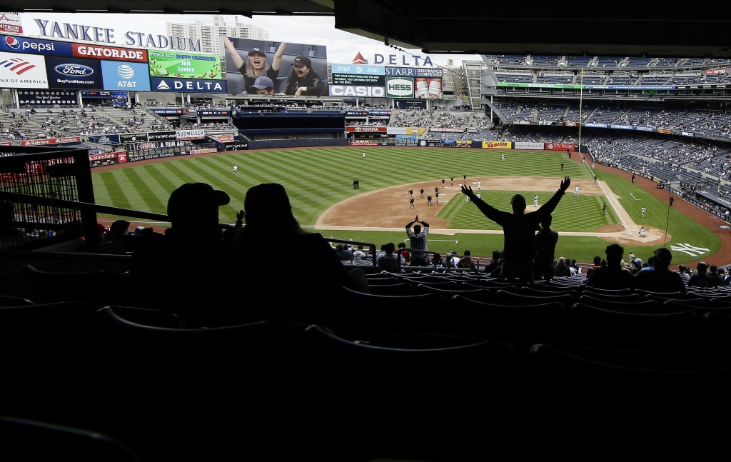 Fans cheer during the seventh inning stretch during in the first baseball game of a doubleheader between the New York Yankees and the Baltimore Oriole