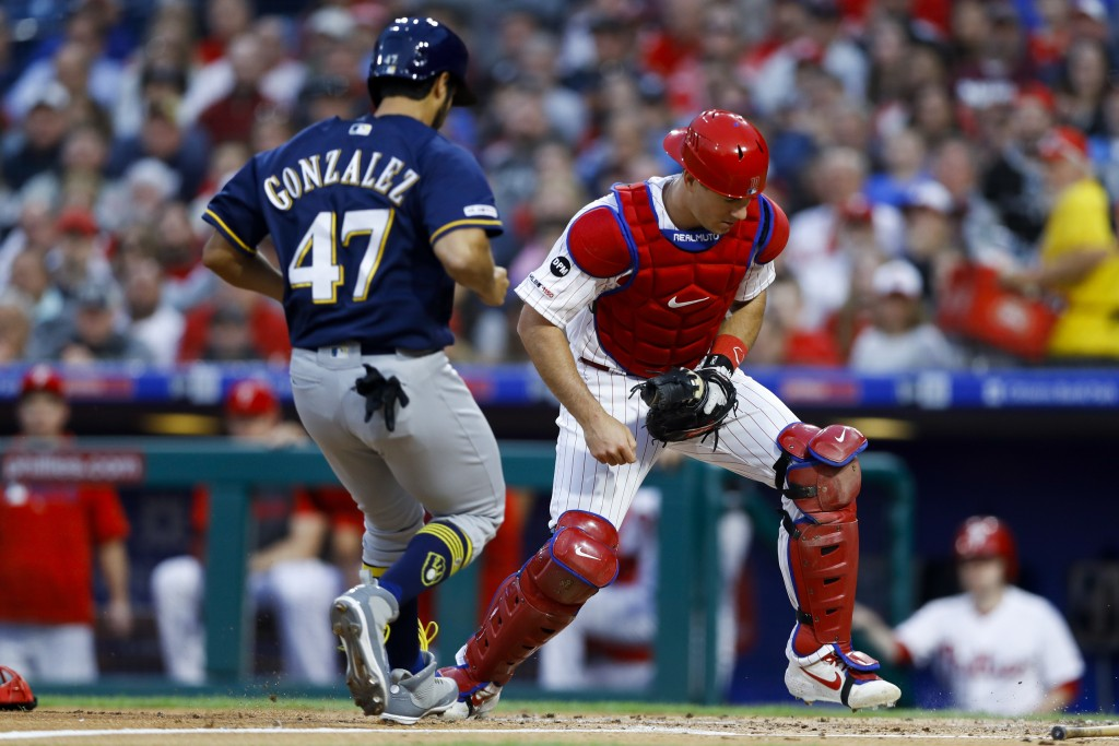 Philadelphia Phillies catcher J.T. Realmuto, right, forces out Milwaukee Brewers' Gio Gonzalez at home on a ball hit by Ryan Braun during the third in...