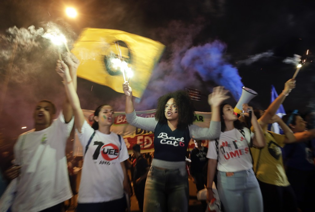 Students light flares as they protest against a massive cut in the education budget imposed by the administration of Brazilian President Jair Bolsonar