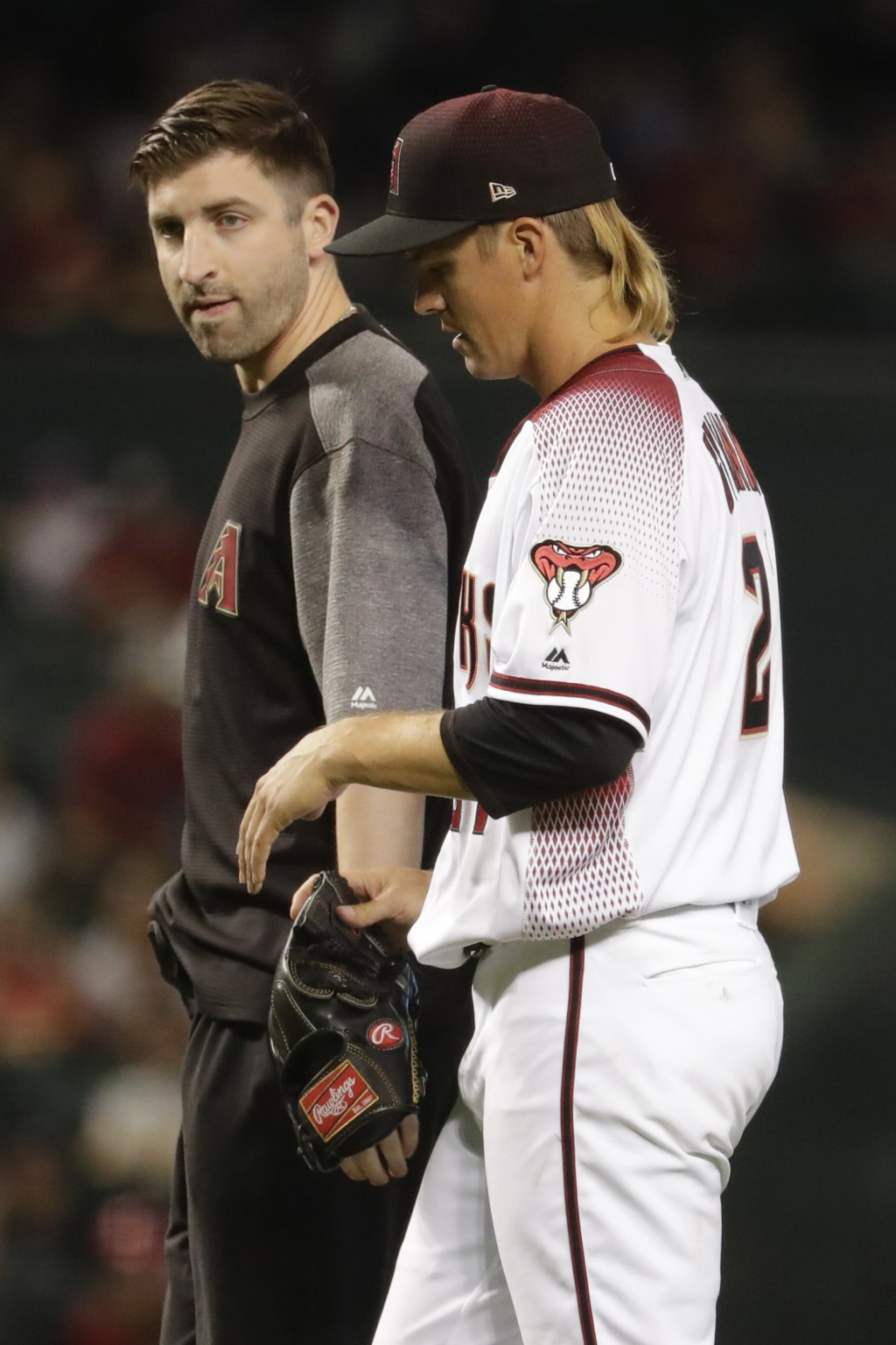 Arizona Diamondbacks starting pitcher Zack Greinke leaves the field with a trainer during the eighth inning of a baseball game against the Pittsburgh