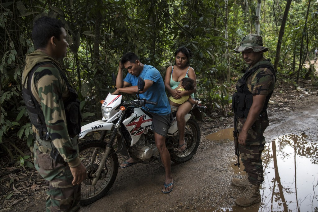 """In this April 3, 2019 photo, """"Operation Mercury"""" policemen question a wildcat miner near the Mega 12 police base in Peru's Tambopata province. The ope"""