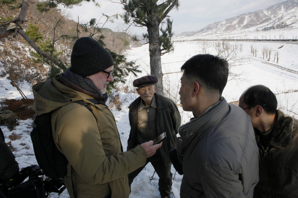 In this Dec. 3, 2015 photo The Associated Press' North Korea Bureau Chief Eric Talmadge, left, speaks to village elder Song Hong Ik, center, about his...