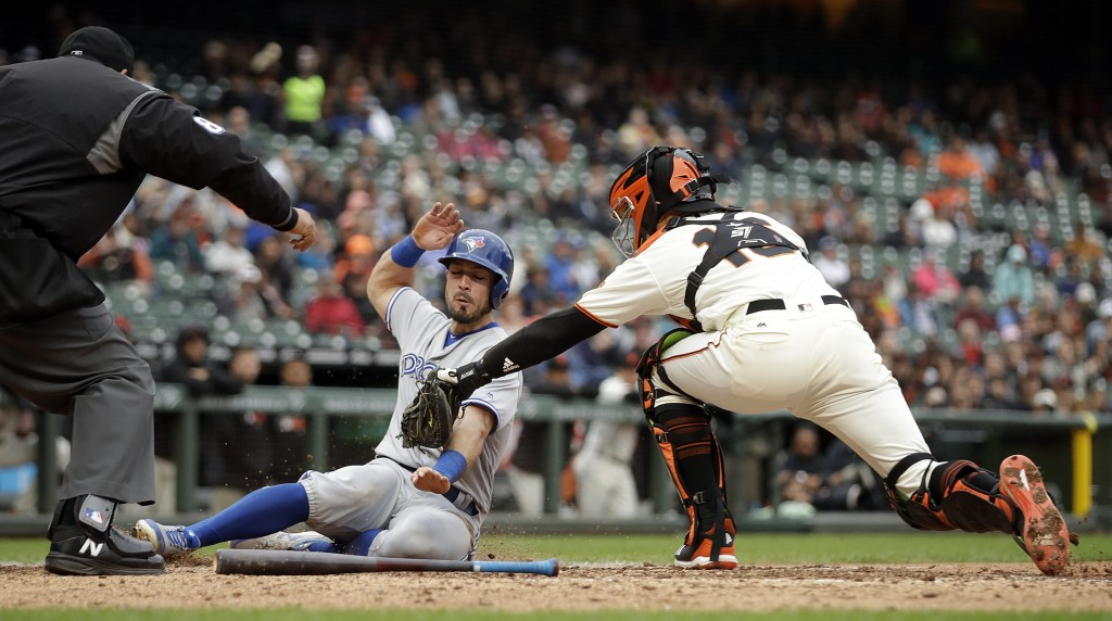 San Francisco Giants catcher Aramis Garcia, right, tags out Toronto Blue Jays' Randal Grichuk at home plate in the sixth inning of a baseball game Wed