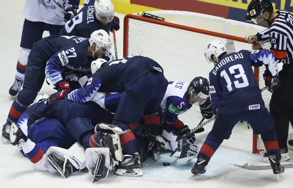 Great Britain's Ben Davies, 2nd right, reaches for the puck during the Ice Hockey World Championships group A match between the United States and Grea