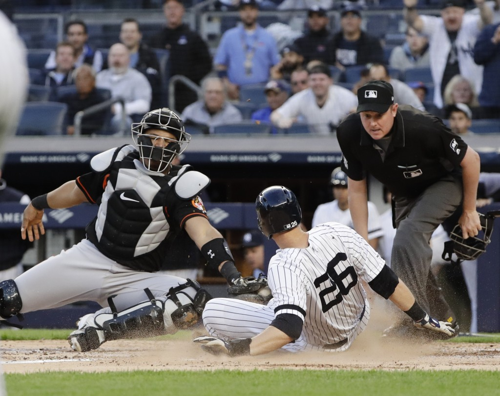 New York Yankees' DJ LeMahieu, right, slides past Baltimore Orioles catcher Pedro Severino, left, to score on a Luke Voit double during the third inni