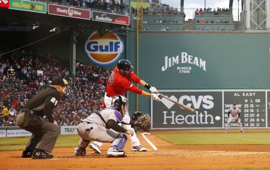 Boston Red Sox's J.D. Martinez connects for an RBI single against the Colorado Rockies during the first inning of a baseball game Wednesday, May 15, 2