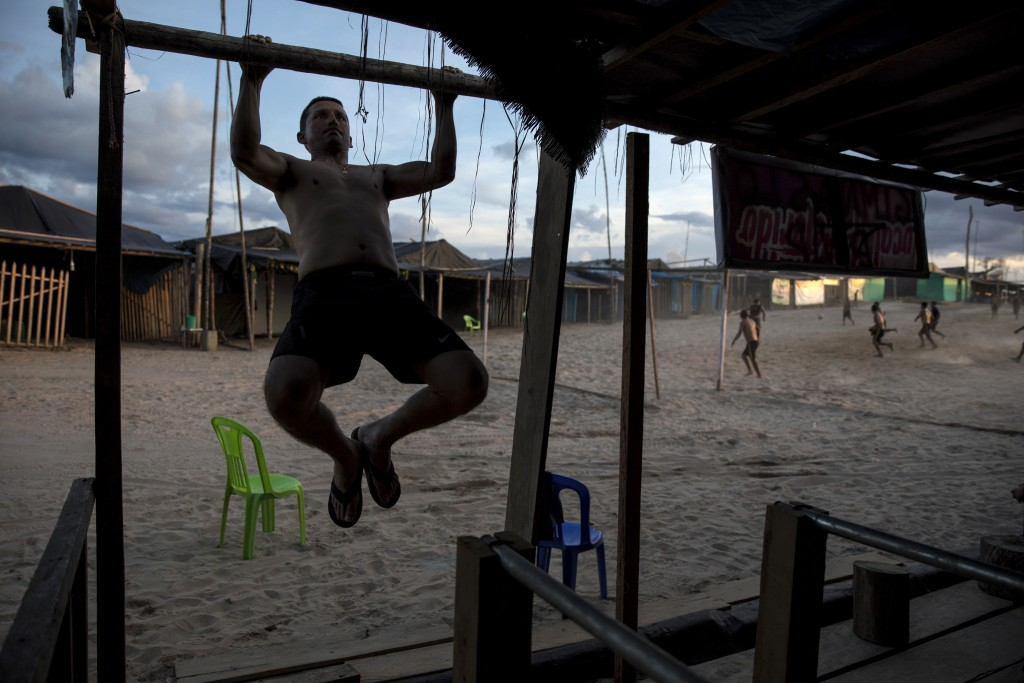 In this March 31, 2019 photo, Maj. Gustavo Cerdeña does pull-ups using the wood frame of a structure at the Balata police and military base, once an i...