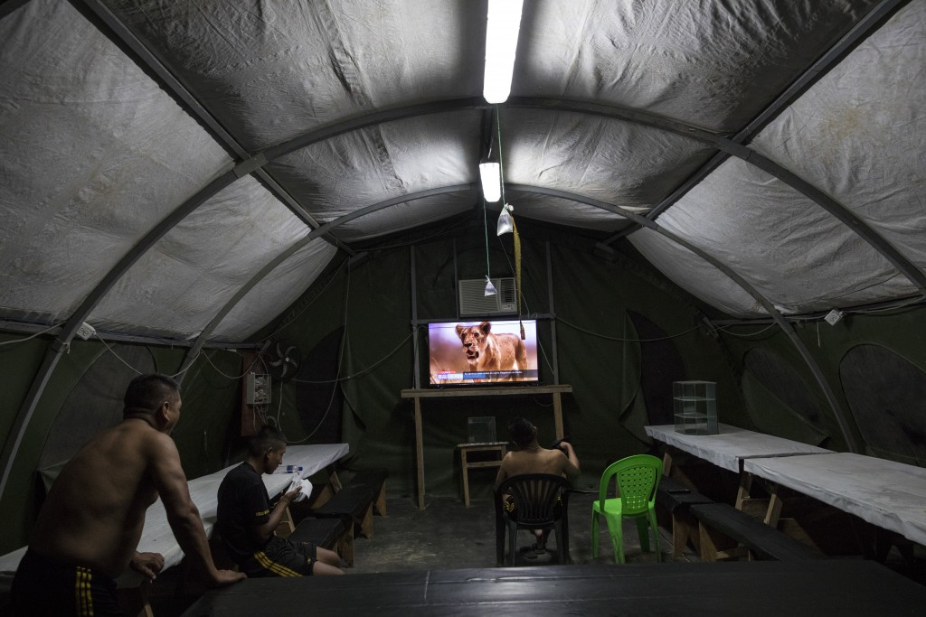 In this March 31, 2019 photo, soldiers watch a nature show in their tent at the Balata military and police base in Peru's Tambopata province. The base