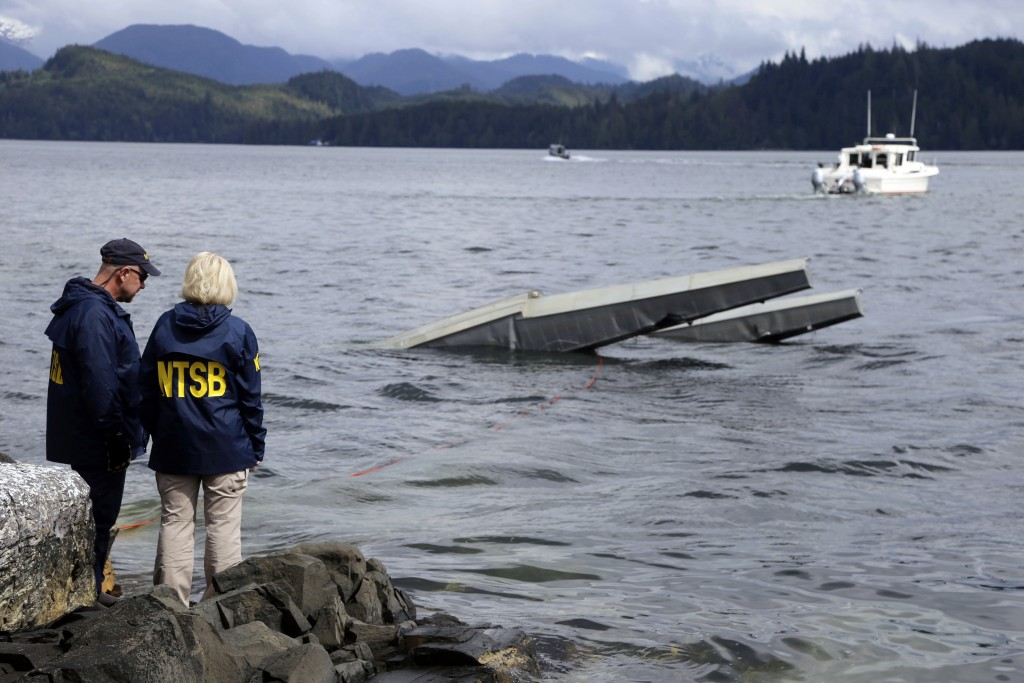 In this photo provided by the National Transportation Safety Board, NTSB investigator Clint Crookshanks, left, and member Jennifer Homendy stand near ...