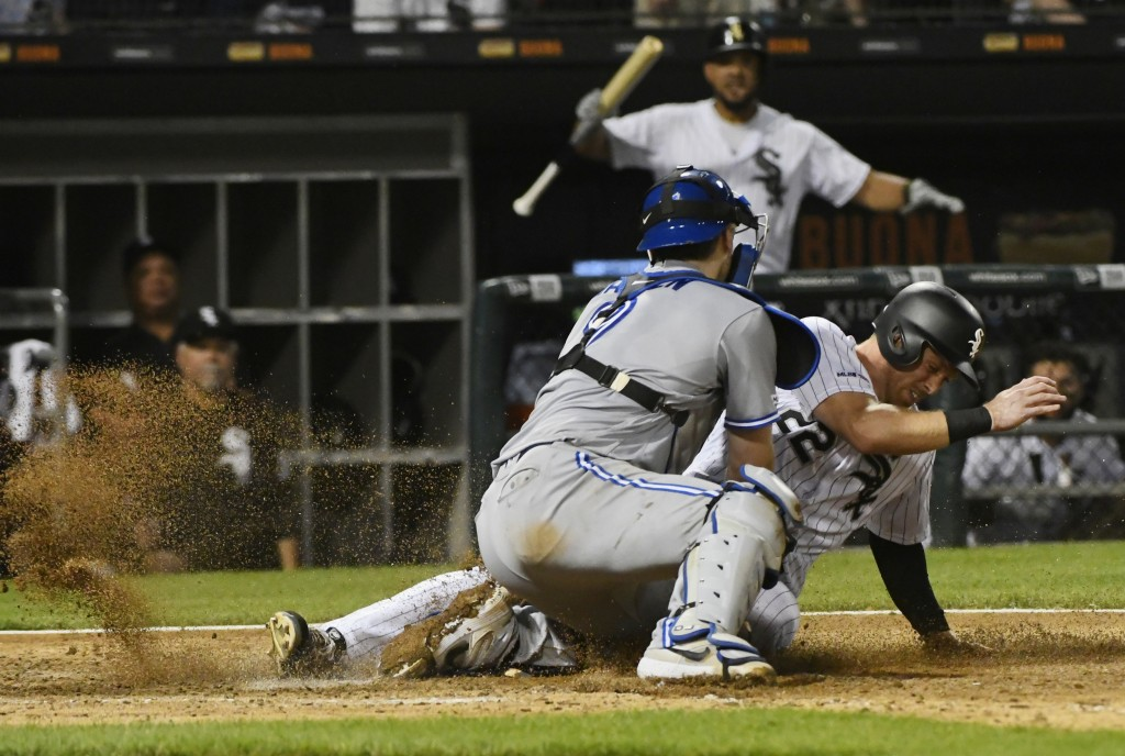 Chicago White Sox's Charlie Tilson (22) scores past Toronto Blue Jays catcher Danny Jansen during the eighth inning of a baseball game Thursday, May 1...