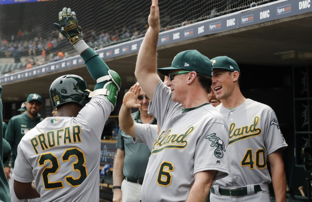 Oakland Athletics' Jurickson Profar is greeted by manager Bob Melvin (6) and starting pitcher Chris Bassitt (40) after hitting a grand slam in the thi...