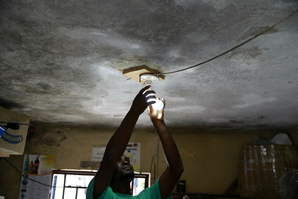 In this April 16, 2019 photo, Johny Legagneur charges a light bulb for a client at his shop in Petion-Ville, Haiti. Johny uses an inverter and generat