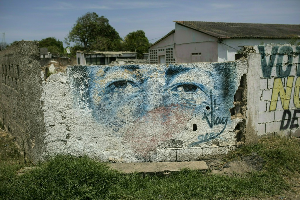 An eroded mural of Venezuela's late President Hugo...