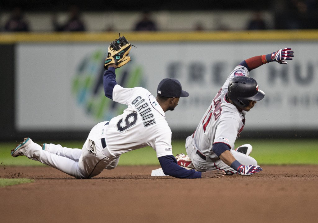 Seattle Mariners second baseman Dee Gordon goes to the ground after tagging out Minnesota Twins' Jorge Polanco, who tried to stretch a single into a d