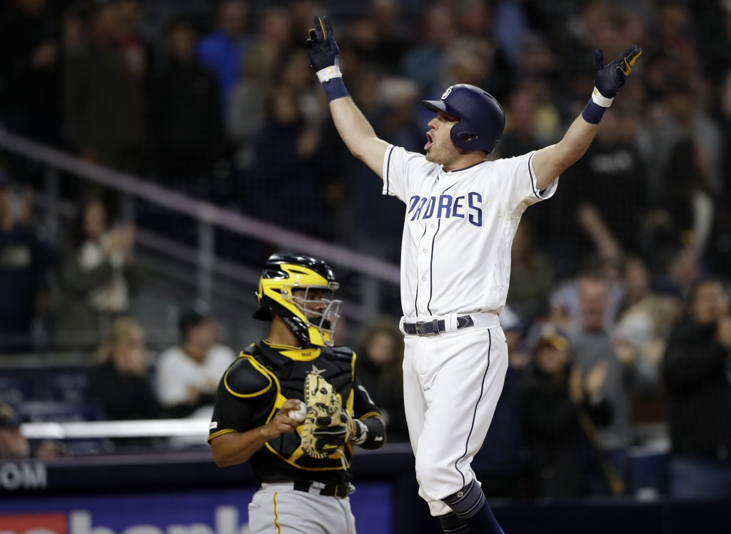 San Diego Padres' Ian Kinsler celebrates after hitting a three-run home run, next to Pittsburgh Pirates catcher Elias Diaz during the sixth inning of