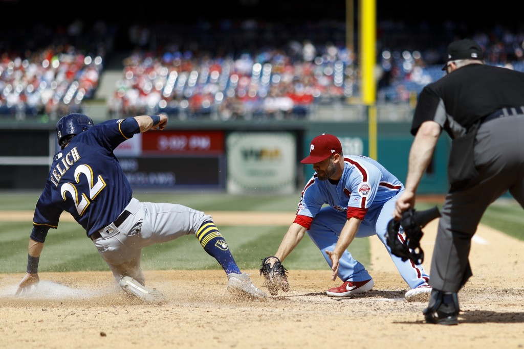 Philadelphia Phillies relief pitcher Adam Morgan, center, tags out Milwaukee Brewers' Christian Yelich, left, after Yelich tried to score on a passed