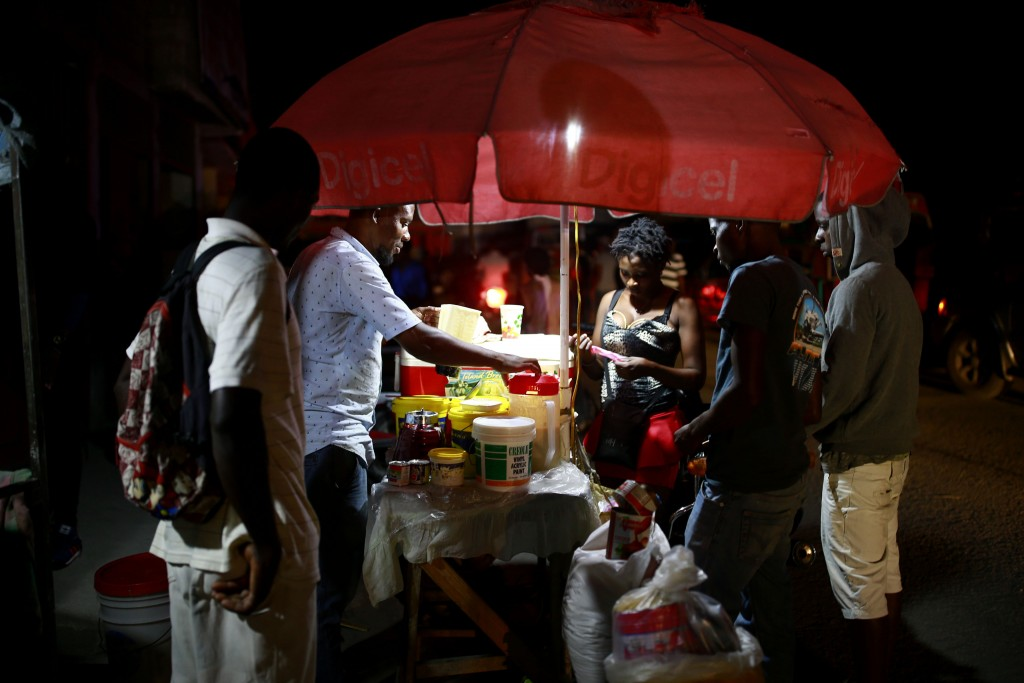 In this April 16, 2019 photo, street vendors sell juice in Petion-Ville, Haiti. The current fuel crisis is helping push Haiti's economy dangerously cl...