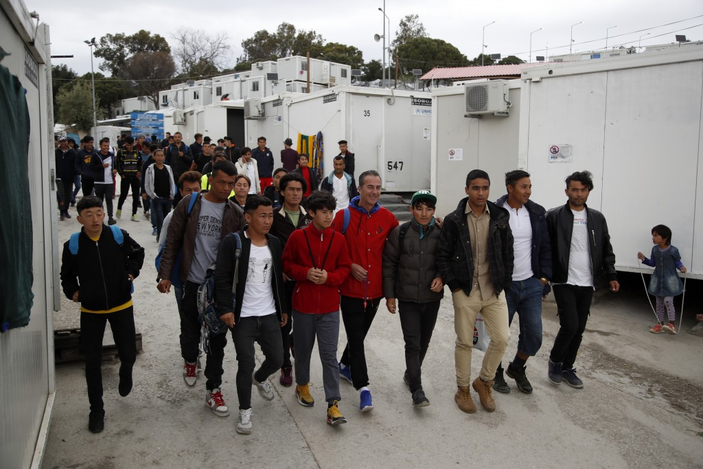 In this Saturday, May 4, 2019, Giorgos Patlakas, center, founder of Cosmos FC accompanied by his players, leaves Moria refugee camp, on the northeaste