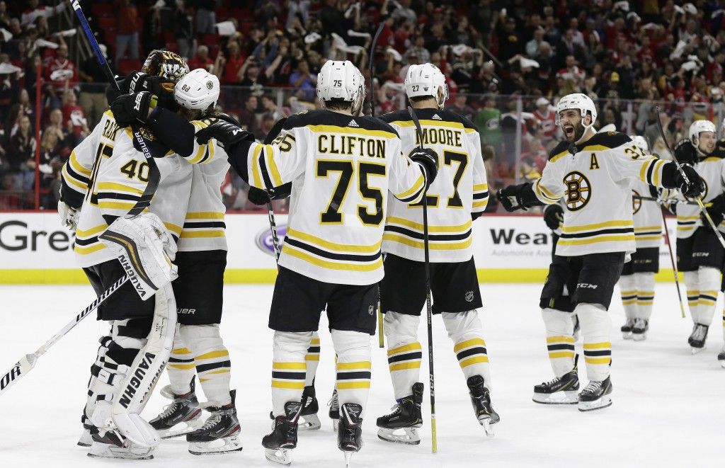 Boston Bruins goalie Tuukka Rask, left, of Finland, is congratulated by teammates following Game 4 of the NHL hockey Stanley Cup Eastern Conference fi