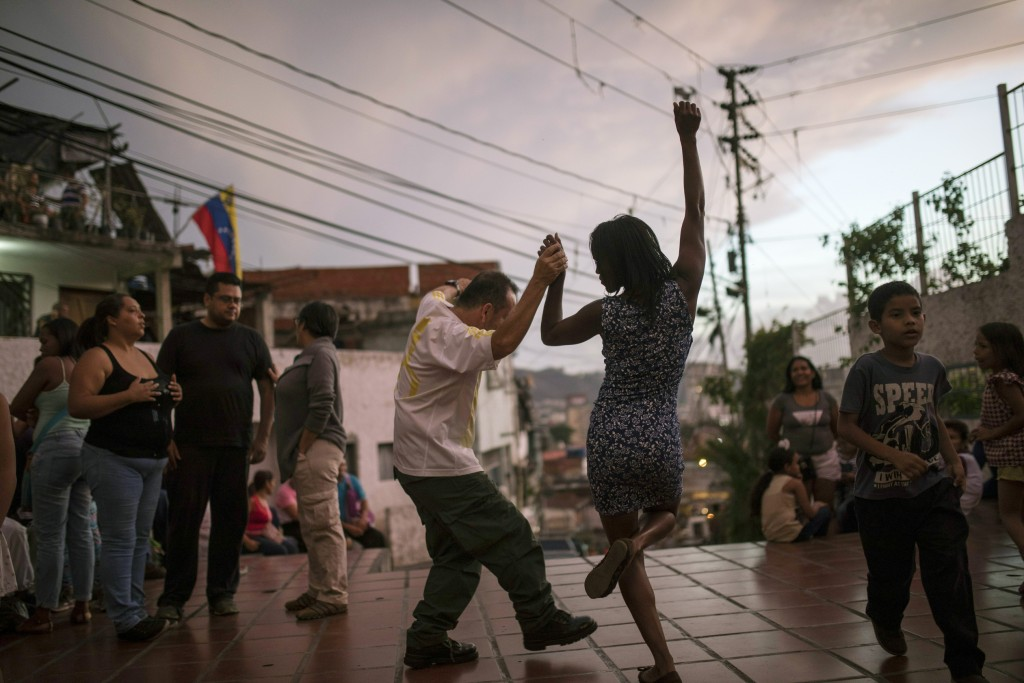In this May 11, 2019 photo, Irene Vaamondez, right, dances with a neighbor as musicians play live music at a public plaza where neighbors socialize in