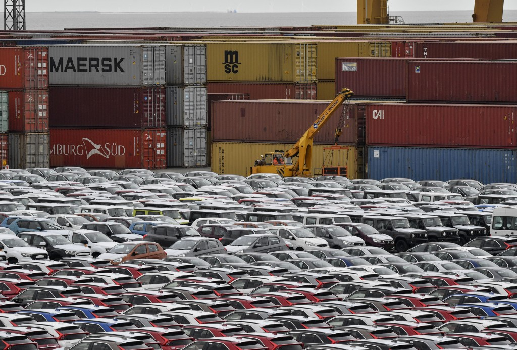 Cars for export and import are stored in front of containers on Thursday, May 16, 2019 at the harbor in Bremerhaven, Germany, with 2 million vehicles ...