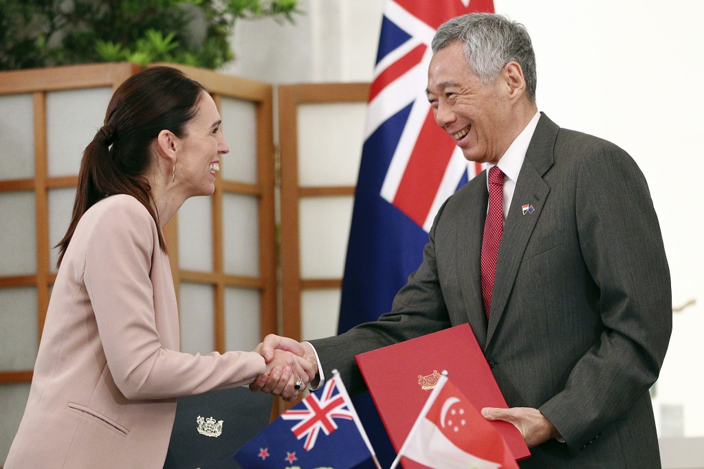 New Zealand's Prime Minister Jacinda Ardern, left, shakes hands with Singapore's Prime Minister Lee Hsien Loong after signing a joint declaration for