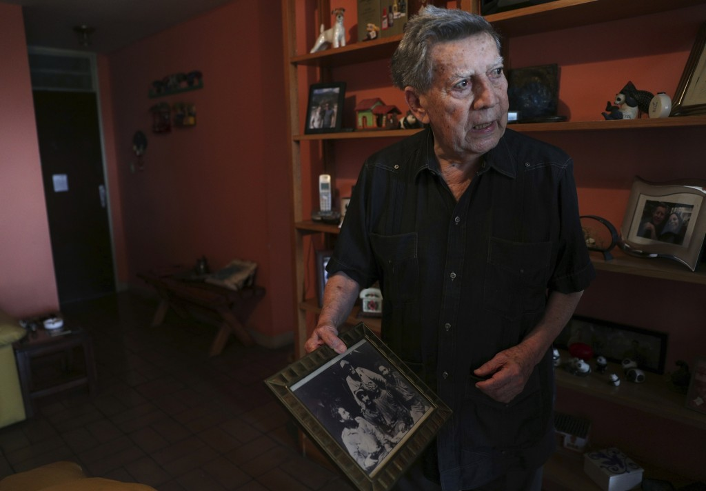 Venezuelan ex-guerrilla Hector Perez Marcano holds an old photo of himself, left, with his fellow rebel soldiers who aided a 1967 Cuban invasion, duri...