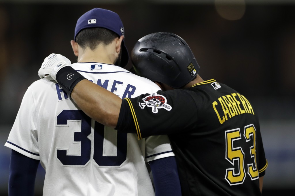 Pittsburgh Pirates' Melky Cabrera, right, embraces San Diego Padres first baseman Eric Hosmer after being walked during the sixth inning of a baseball