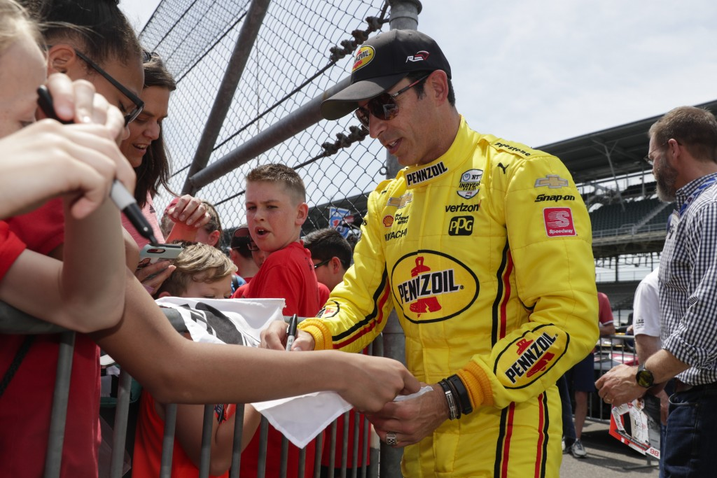 Helio Castroneves, of Brazil, signs autographs for fans during practice for the Indianapolis 500 IndyCar auto race at Indianapolis Motor Speedway, Thu