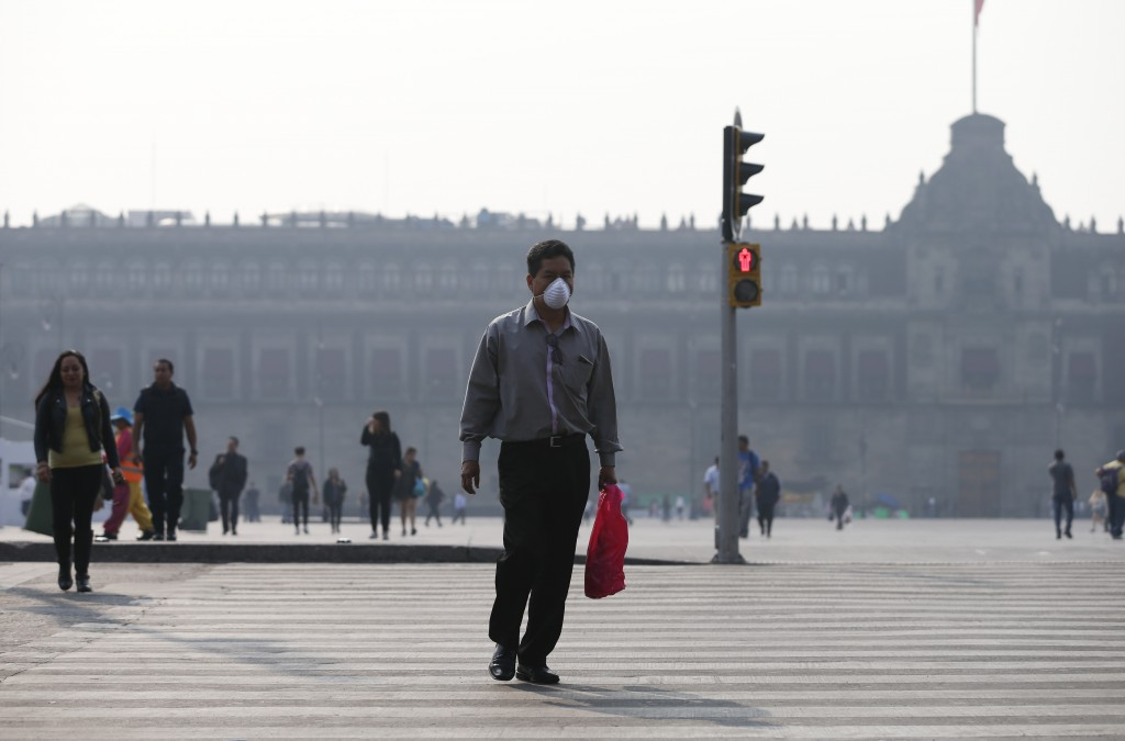 A man wearing a face mask crosses a street backdropped by the National Palace shrouded by haze, in the Zocalo, Mexico City's main square, Thursday, Ma