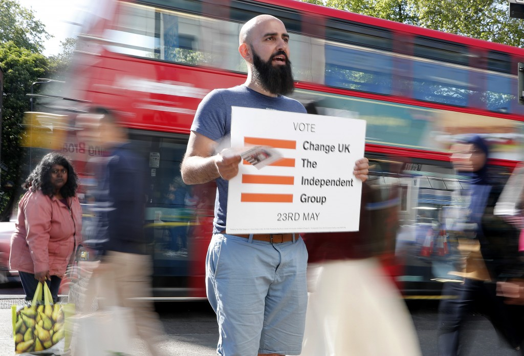 In this Tuesday, May 14, 2019, photo, a supporter of Change UK party holds a poster advertising for voting in the European election in London. An elec