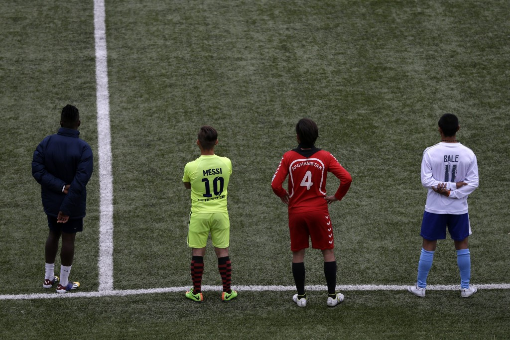 In this Saturday, May 4, 2019, Francis Kalombo from Congo, left, and Afghan migrants watch a friendly match between African team and Afghan migrants a...