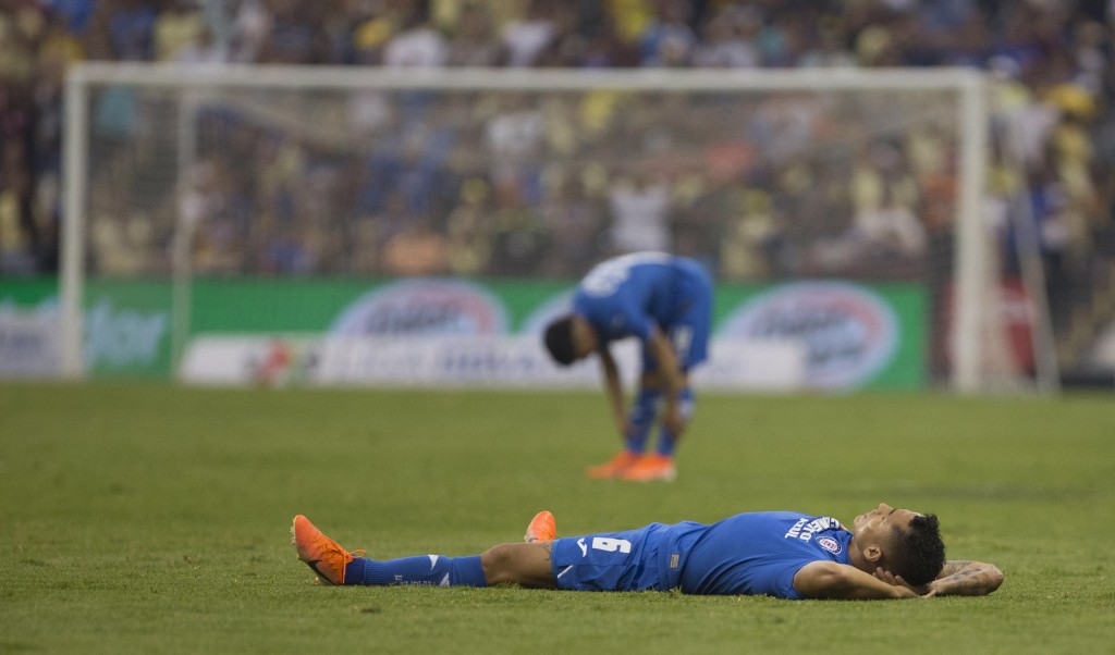 In this May 12, 2019 photo, Cruz Azul's Victor Yotun lies on the field after his team lost 1-0 to America at a Mexico soccer league match in Mexico Ci