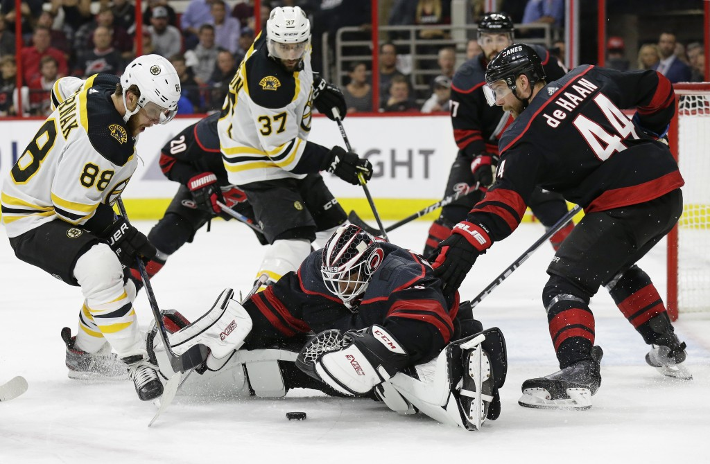 Boston Bruins' David Pastrnak (88), of the Czech Republic, and Patrice Bergeron (37) look to score on Carolina Hurricanes goalie Curtis McElhinney whi