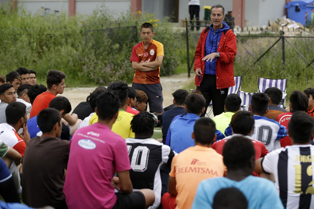 In this Saturday, May 4, 2019, Giorgos Patlakas, right, founder of Cosmos FC gives directions to his players, at a soccer field in Moria village, on t...