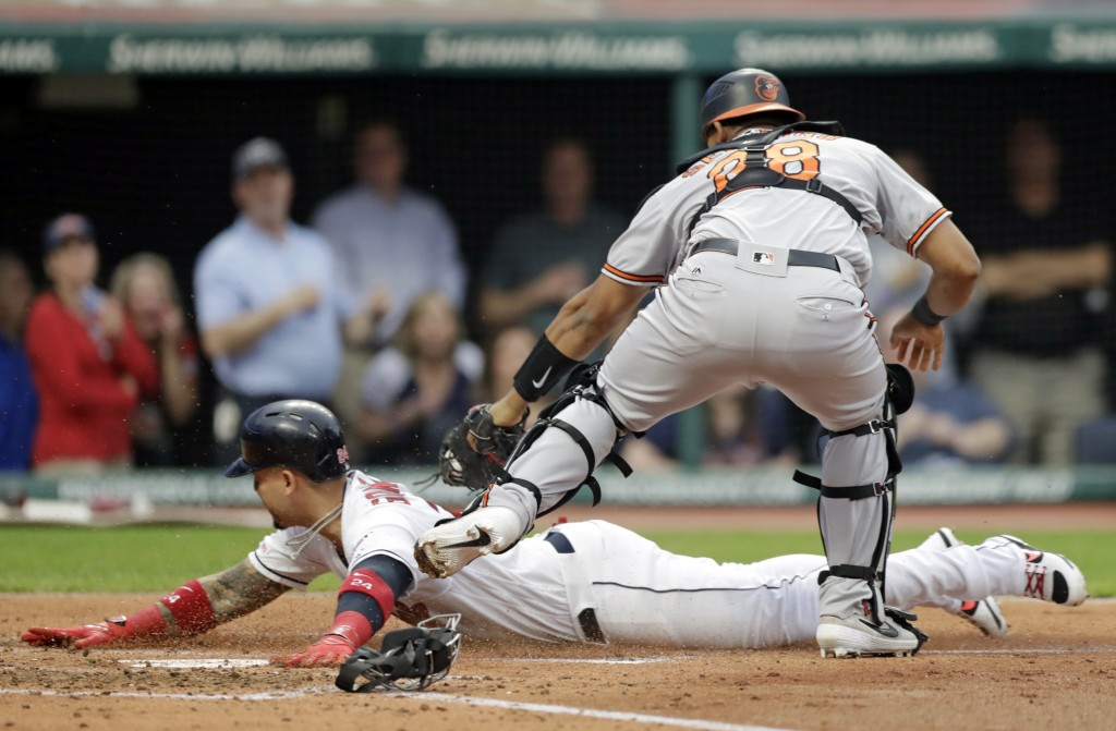 Cleveland Indians' Carlos Gonzalez is caught stealing home plate as Baltimore Orioles' Pedro Severino tags him out in the third inning of a baseball g