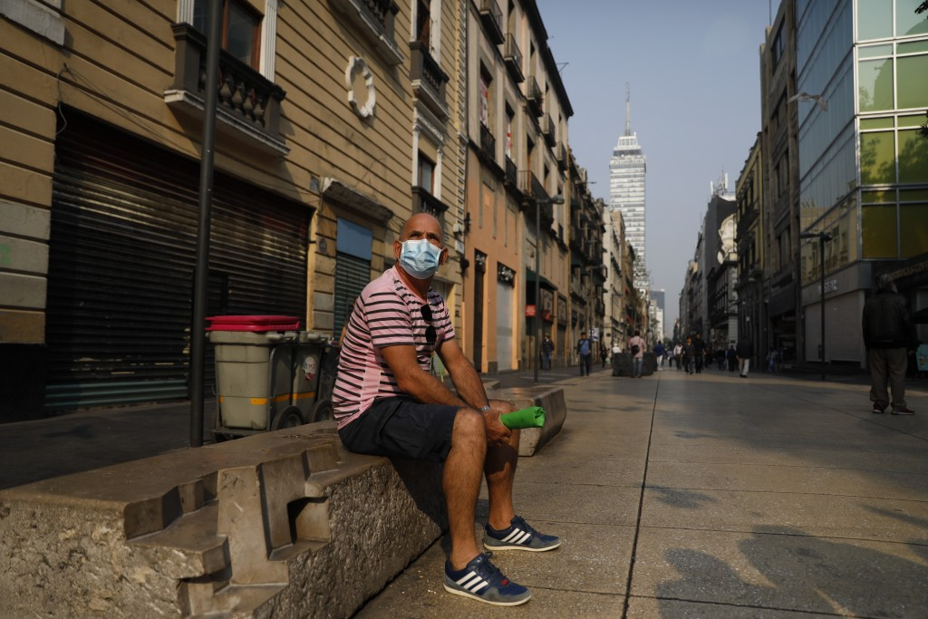 Cuban tourist Fernando Castillo wears a face mask as he sits on a bench on pedestrian Madero Street in the historic center of Mexico City, Thursday, M