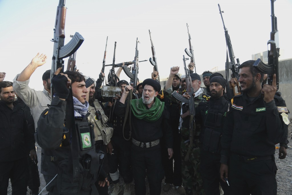 FILE - In this March 14, 2015 file photo, Iraqi Shiite militia group called Imam Ali Brigades chant slogans against the Islamic State group at the bat